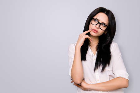 Young successful woman in spectacles has new idea and think about it. She looks to the side on copy space