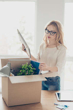 Vertical portrait of upset fired woman in glasses packing up her stuff into cardboard box at office