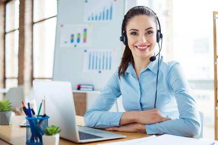 retrato de mujer joven linda en camisa azul y auriculares sentado en la mesa y trabajando con ordenador Foto de archivo