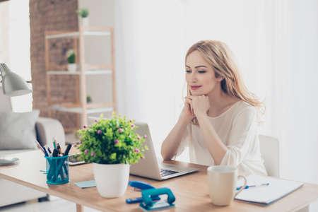 自宅のコンピューターと作業中のテーブルに座って幸せかわいいきれいな女性 写真素材