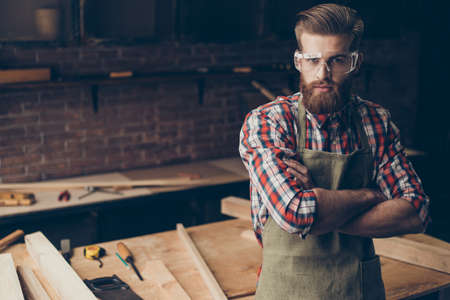 Bearded handsome joiner  think and look at camera near tabletop with tools.  Stylish young entrepreneur with brutal hairstyle and saved glasses crossed hands at his workstation