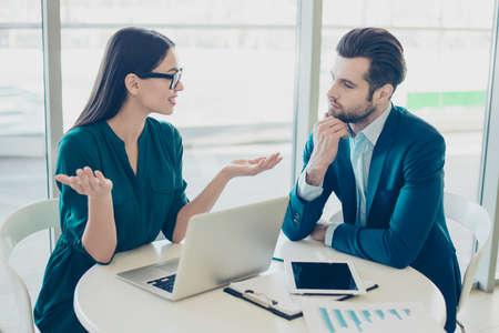 Foto van twee jonge slimme serieuze zakelijke partners die een vergadering hebben en hun bedrijfsplannen bespreken en welke strategie in de nabije toekomst moet worden gekozen