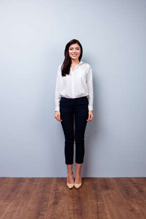 Full-length photo of front view of young confident businesswoman on gray background