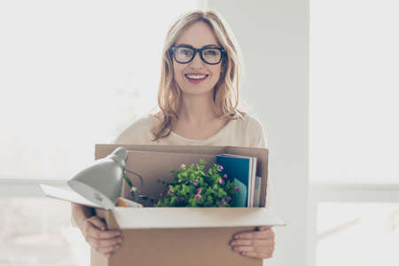 Concept of promotion at work. Young dreaming pretty smiling woman in glasses holding her belongings in cardboard box Фото со стока