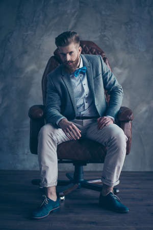 stylish serious minded brutal young man with red mustache, beard and beautiful hairstyle ponder while sitting on  comfortable office arm-chair and wearing formal clothes and trendy shoes