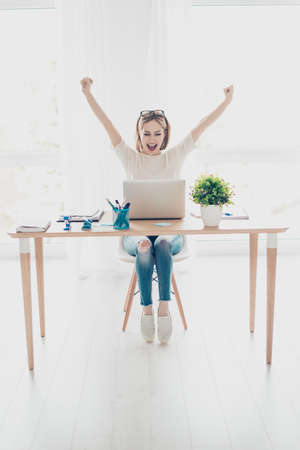 triumphing: Happy excited successful businesswoman triumphing sitting in the workplace