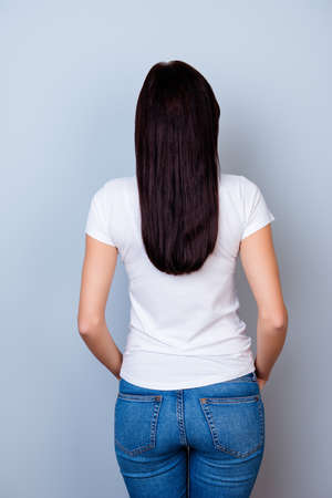 Rear view of cute young woman on gray background