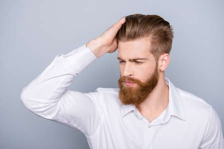 Portrait of confident man with red beard touching his hair