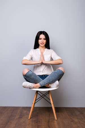 Beautiful young woman sitting on chair in lotus pose against gray background Stock Photo