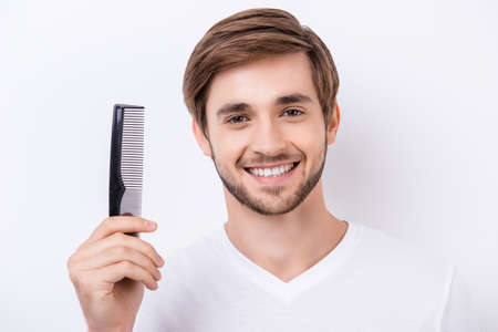 Portrait of handsome cheerful bearded young man showing his black comb while standing white background