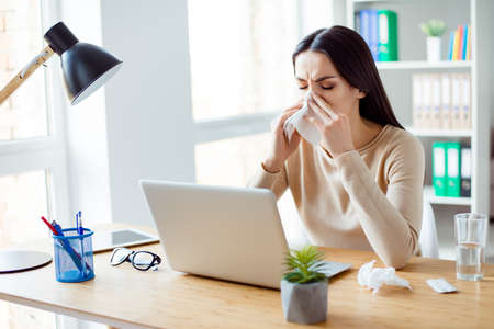 running nose: Ill woman sitting at the table with computer at work and using napkin