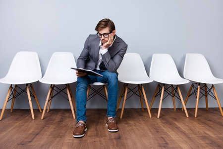 Young stylish man is holding documents while sitting on white chair. He is the last in the queue for an interview for a new job Stock Photo