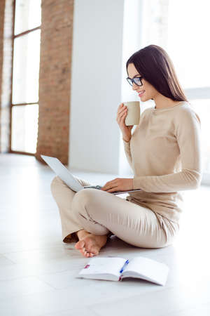 Freelance concept. Young successful woman working at home while sitting on the floor with laptop and coffee. Designer has idea and plan how to decorate new apartment Stock Photo - 78158760