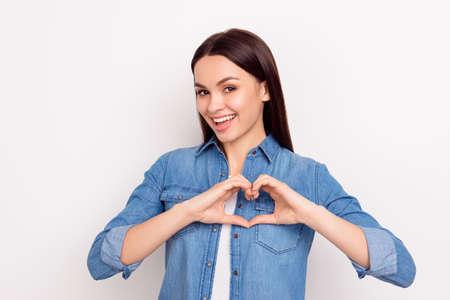 손가락으로 마음을 만들고 웃는 사랑에 귀여운 소녀 스톡 콘텐츠