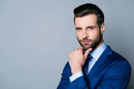 파란색 양복과 턱을 만지고 넥타이에 심각한 유행 잘 생긴 남자의 초상화 스톡 콘텐츠