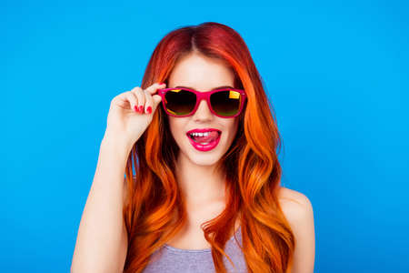 Funny carefree girl with ginger hair holding sunglasses and licking pink lips while standing on blue background Zdjęcie Seryjne