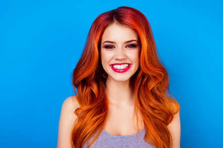 maquillage: Close-up of attractive cute girl with long ginger fair hair with toothy beaming smile while standing on blue background