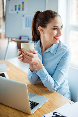 Vertical photo of glad cheerful woman with beaming smile drinking coffee during rest time Stock Photo