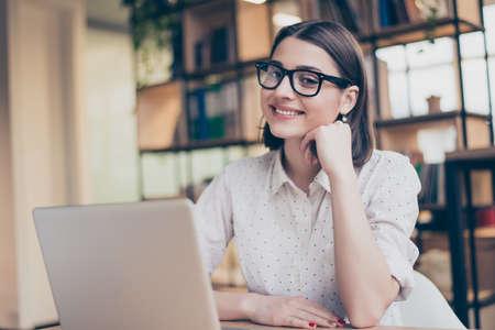 陽気な笑みを浮かべてスマート若いかなりモダンなワークスペースのラップトップで座っている女性 写真素材