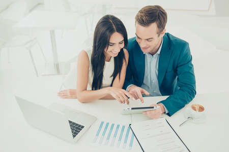 Two young business people working on new project.  Man shows a woman the advantages of investing in his company Stock Photo