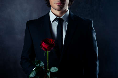 Close up of man in black suit holding red rose
