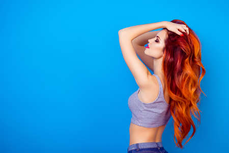 Portrait of sexual  charming stylish girl with long ginger fair hair touching head, dreaming and relaxing