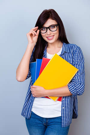 erudition: Portrait of happy student girl in glasses holding notebooks in hands Stock Photo