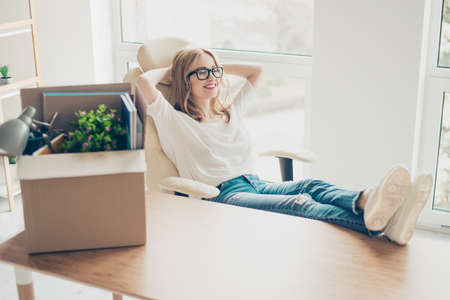 Concept of promotion at work. Young cute smiling woman sitting  in armchair at new office with her feet on the table and rest