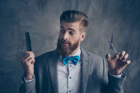 Portrait of Stylish young bearded man in a suit with bow-tie stands on a gray background and chooses between scissors and a comb. He solve going to the barbershop