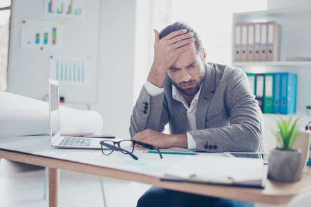 피곤한 젊은 과로 사업가 머리를 터치하고 강한 고통을 느낀다.