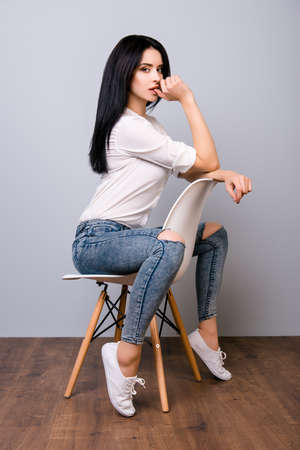 Beautiful sexual young woman posing and biting finger while sitting on white modern chair Stock Photo