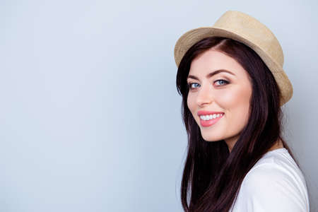 Close up portrait of beautiful smiling woman in hat isolated on gray background