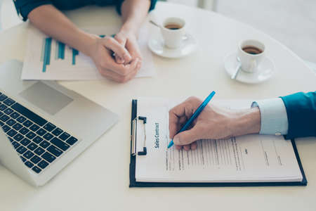accommodation broker: Workplace concept. Top view on mans hand holding a pen and signing a contract Stock Photo