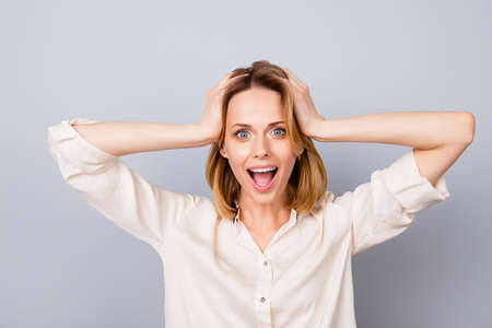 Wow! Its unbelievable! Shocked happy woman with opened mouth touching her head isolated on gray background
