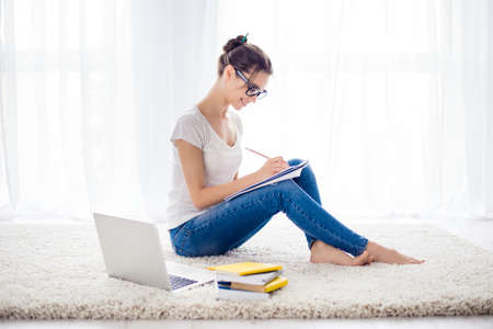 Happy teen is learning at home sitting on a cozy carpet at bright room Stock Photo - 80578232