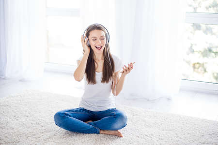 Happy young girl is enjoying listening to the music with headphones at home on white background