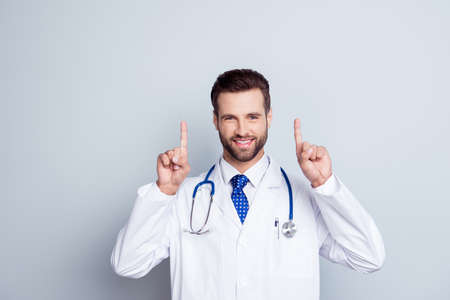 Smiling happy doctor in white coat with stethoscope isolated on gray background pointing up Stock Photo