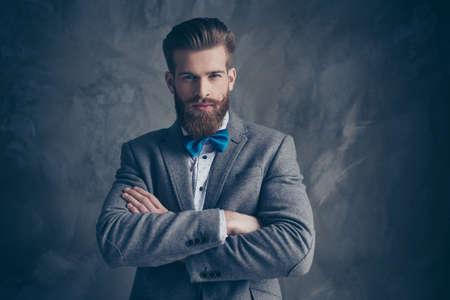 Porträt des ernsten jungen bärtigen Mannes mit Schnurrbart in einem Anzug steht auf einem grauen Hintergrund mit den gefalteten Händen und betrachtet teilweise