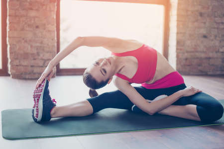 Young fit sportswoman stretching on the mat on the floor. She is relly bendy and flexible as a result of her regular trainings Stock Photo