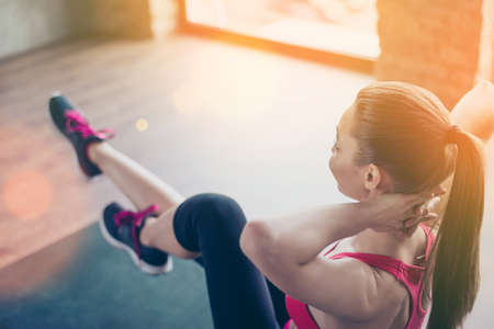 Love sport. Close up photo of girl training on the green mat in sunny room. Girl is wearing sportsclothes and sneakers Stock Photo