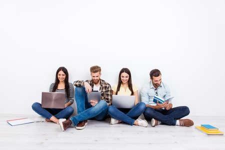 Groep vriendschappelijke glimlachende studenten die op de vloer zitten en moderne technologie voor het bestuderen gebruiken Stockfoto