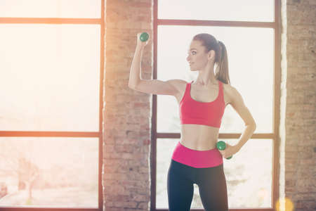 Young sportgirl is working out with dumbbells in bright warm room. Side portrait of satisfied girl, who feels healthy and full of energy Stock Photo
