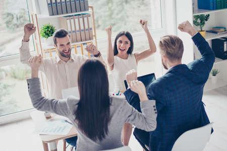 Lo hicimos! Éxito y ganar concepto - equipo de negocios feliz con levantó las manos en la estación de trabajo moderna de luz, celebrando el avance en su empresa Foto de archivo - 80494125