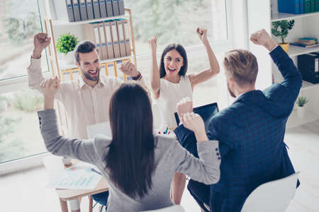 associate: We did it! Success and winning concept - happy business team with raised up hands in light modern workstation, celebrating the breakthrough in their company