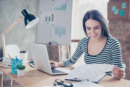 Giovane donna di affari che si siede all'ufficio che lavora con il computer e che analizza i documenti Archivio Fotografico - 80619084