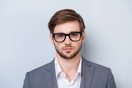 bristles: Portrait of serious young man in glasses looking straight in camera with deep glance in formal clothes on light blue backgroung