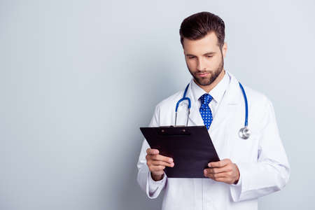 Concentrated medico in uniform holding clipboard and reading information written there Stock Photo