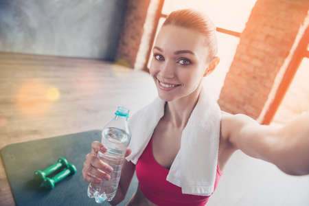 Close up portrait of beautiful cheerful girl in gym. She is making selfie with camera on her device, smiling and holding beverage
