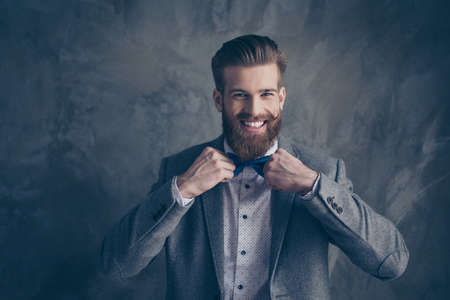 Happy young happy bearded man with mustache in formalewear stands on a gray background and holds his bow-tie with both hands