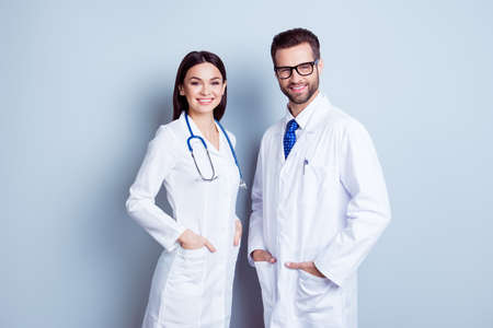 주머니에 자신의 손을 잡고 함께 회색 배경에 서있는 흰 코트에 두 명의 최고의 똑똑한 전문 웃는 의사 노동자